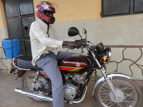Komakech Chritopher using the new motor cycle.JPG
